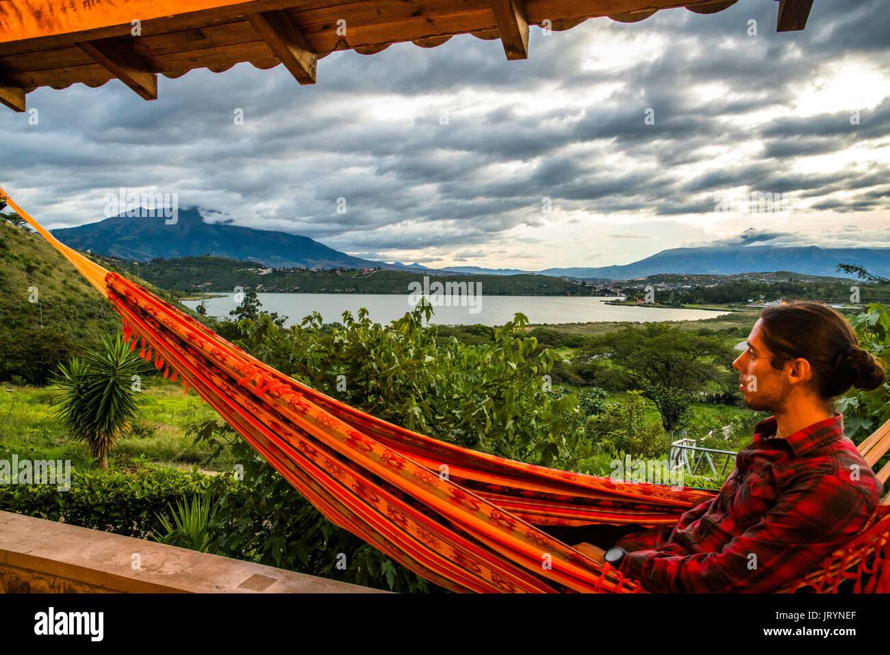 A young traveler enjoying the sunset while overlooking Laguna de Yahuarcocha and Imbabura in Ibarra, Ecuador. - Stock Image