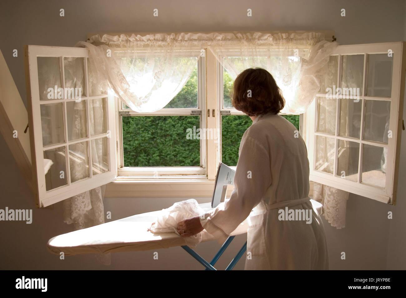 Ironing and house chores. - Stock Image
