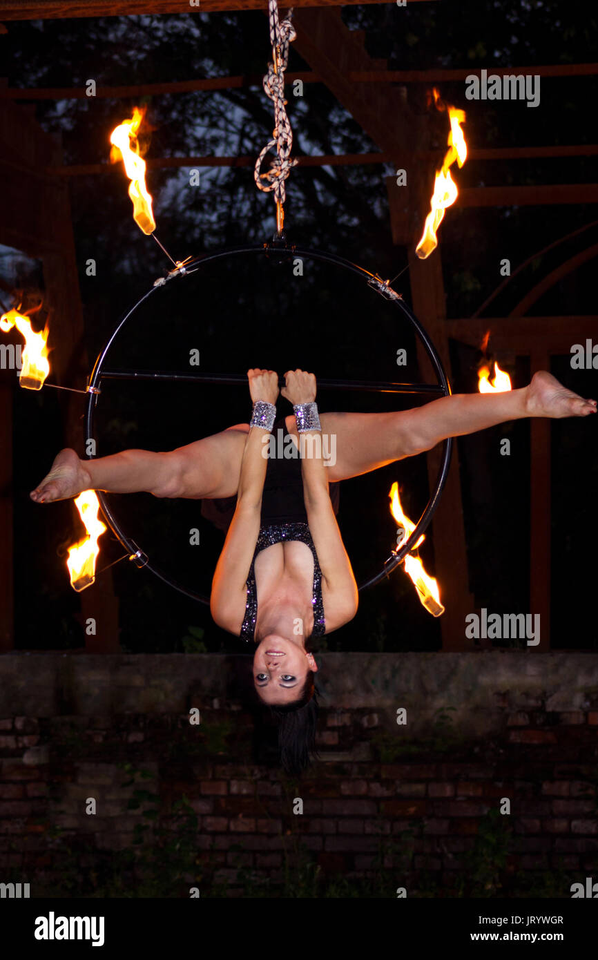 Beautiful aerialist girl doing some tricks on aerial ring with palm torches - Stock Image