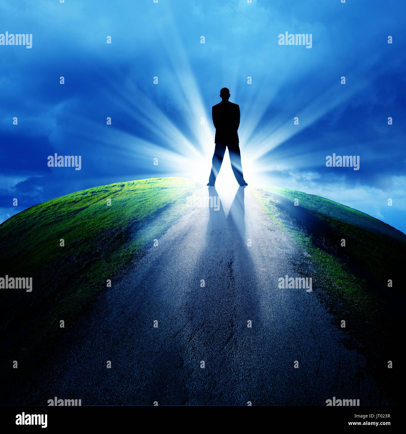 conceptual image of silhouetted businessman on empty road over cloudy sky with beam of light - Stock Image