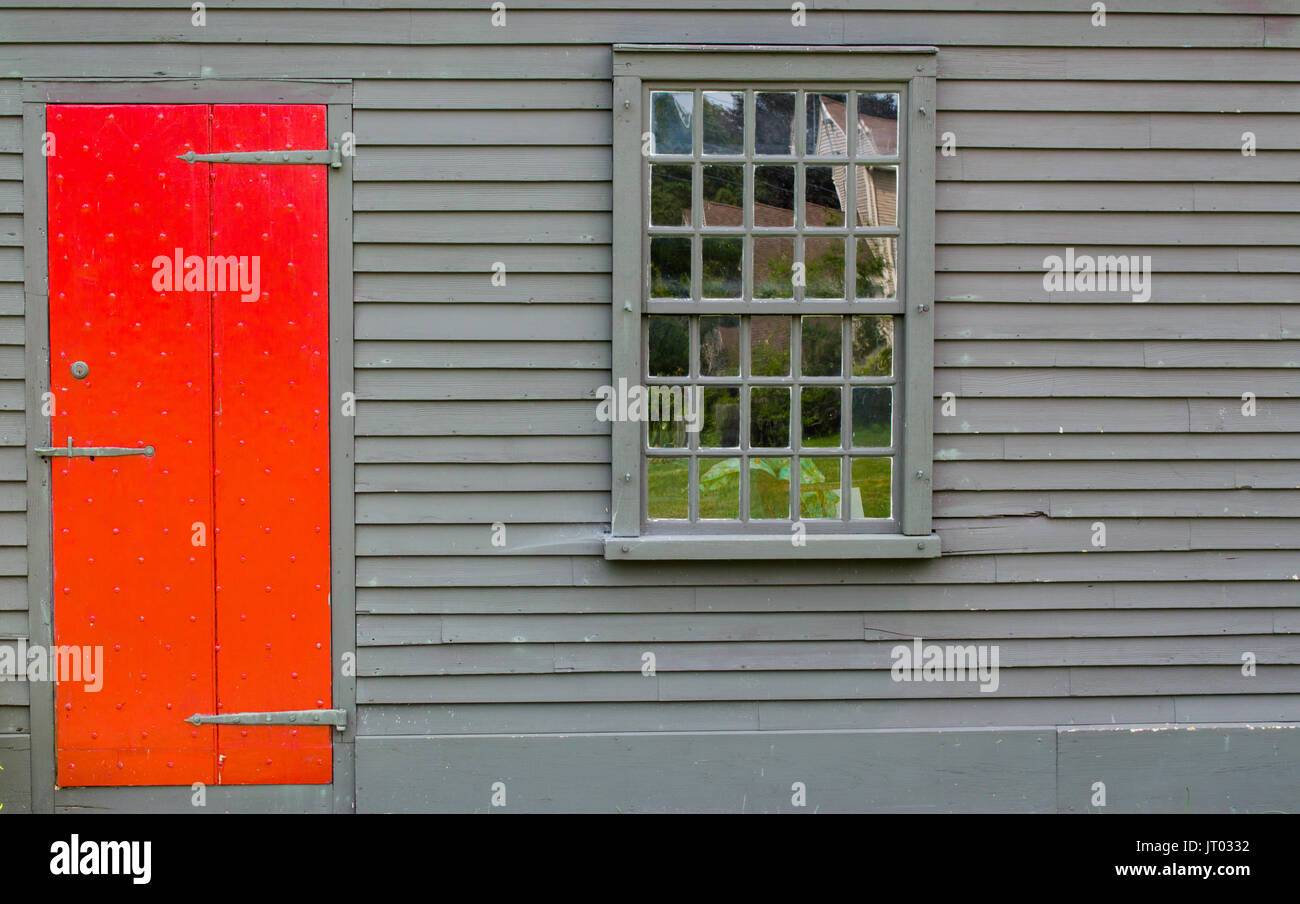 bright red door in brown wall of colonial building with multipaned window - Stock Image