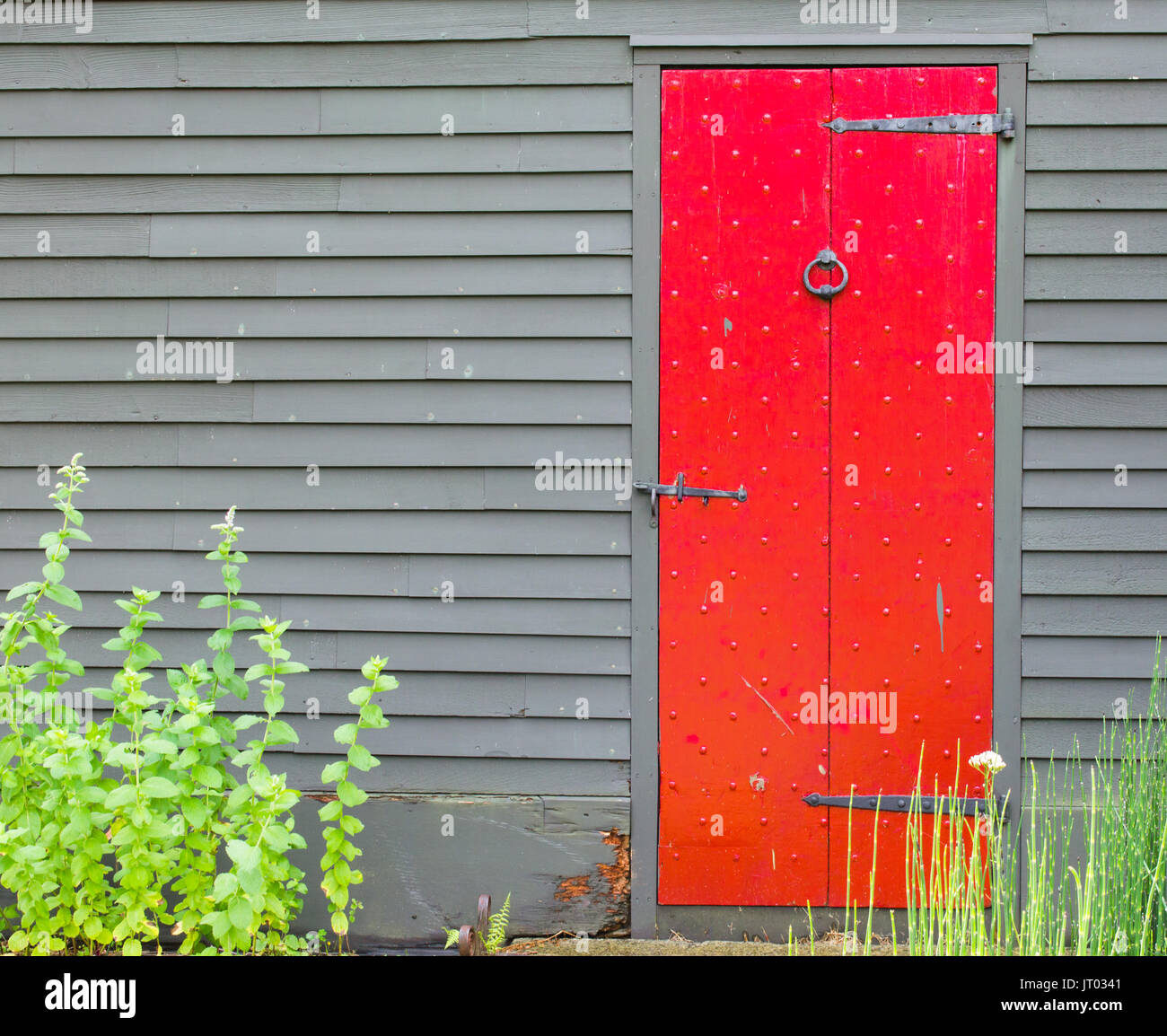 bright red door in brown wall of colonial building - Stock Image