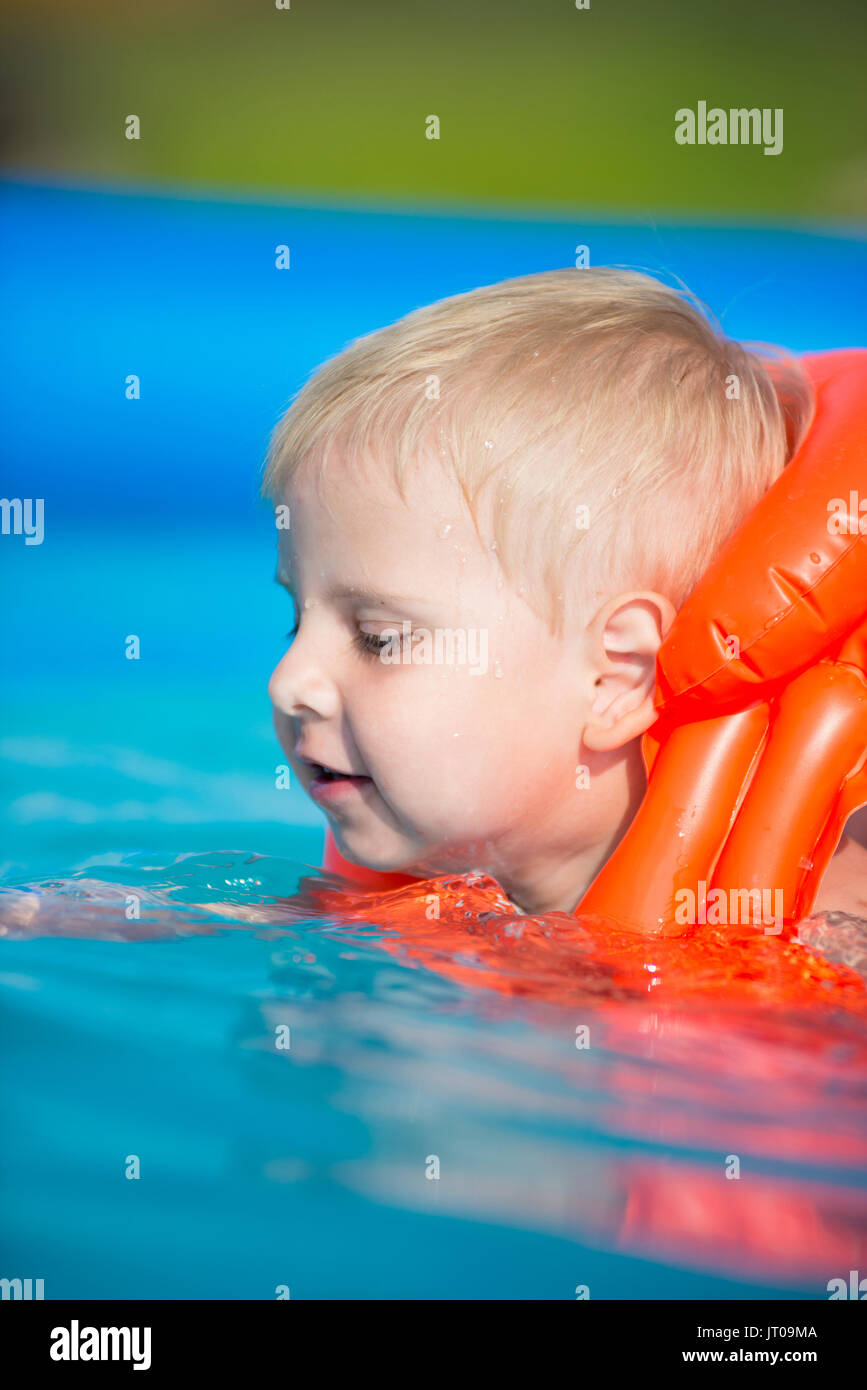 7567381ff0 Pretty little boy in swimming pool. Snorking in the outdoor pool in orange  life jacket