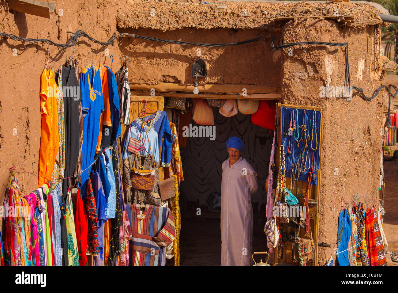 Moroccan traditional clothing store and handicrafts. Ksar Ait Benhaddou, old Berber adobe-brick village or kasbah, Ouarzazate Province. UNESCO World H - Stock Image