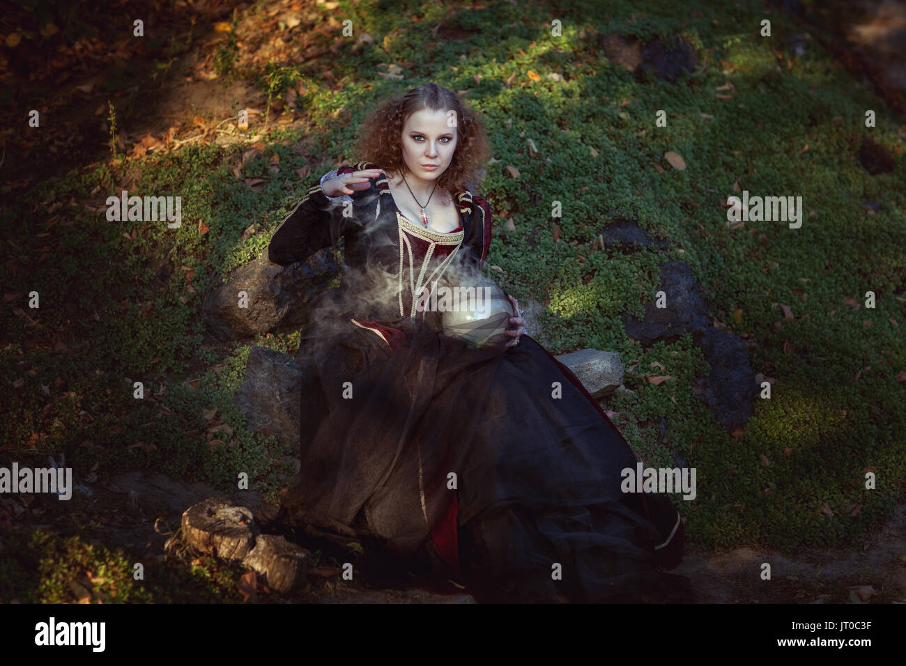 Woman is engaged in magic, she cooks a magic potion. - Stock Image