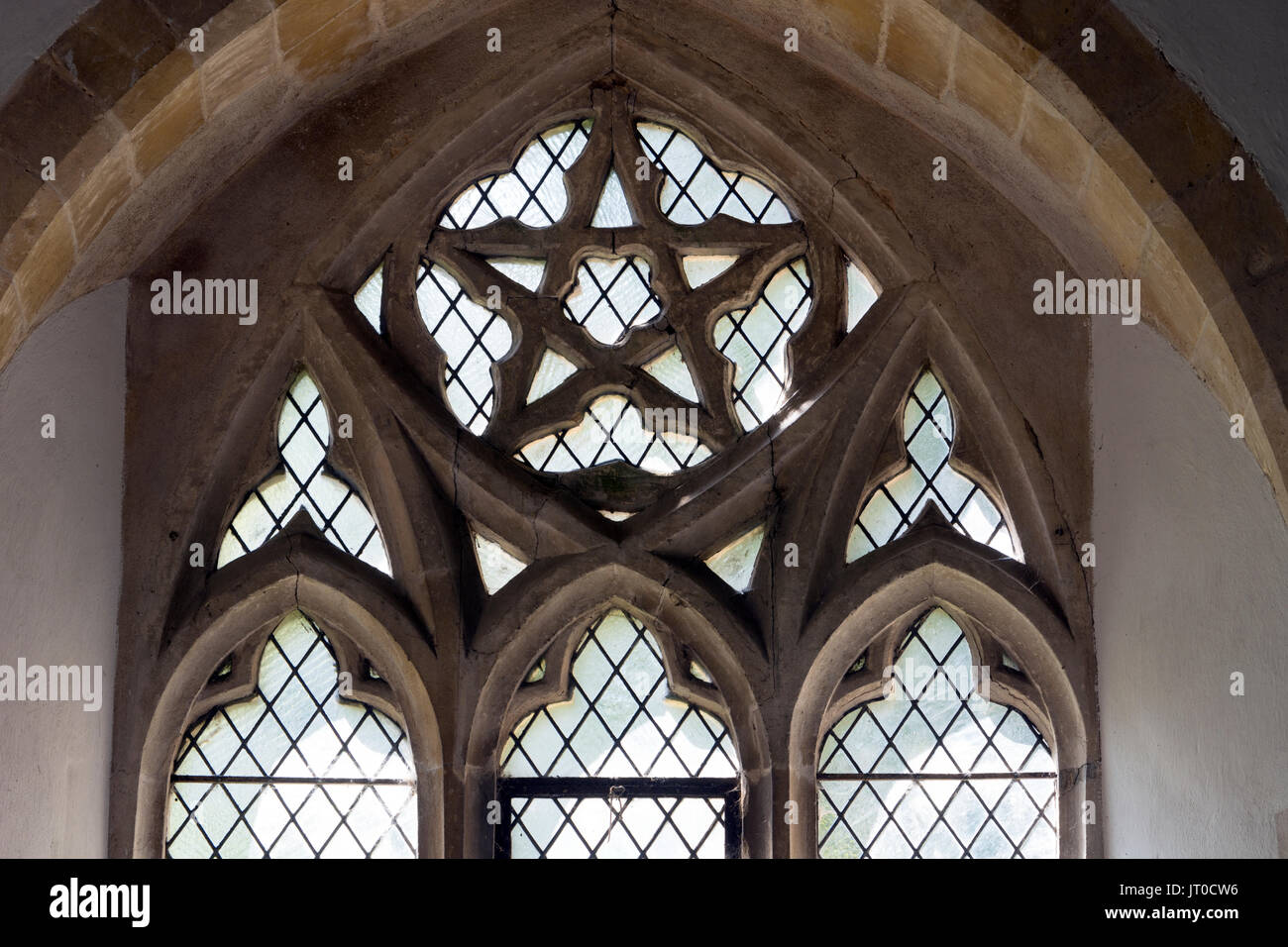 South aisle window tracery including a pentagram, St. Botolph`s Church, Stoke Albany, Northamptonshire, England, UK - Stock Image