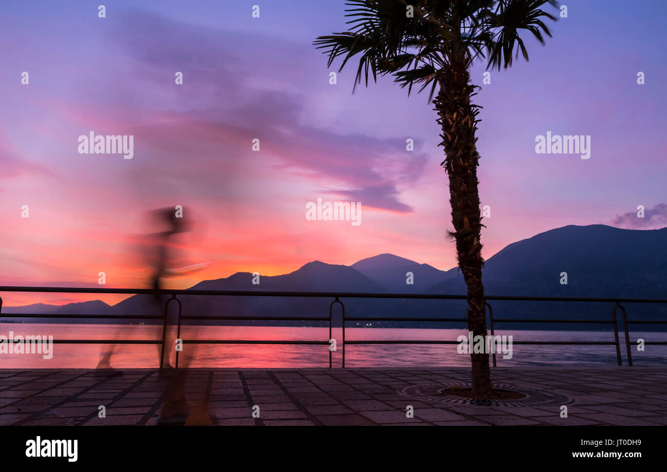 Beautiful foggy sunset at Iseo lake, Lombardy, Italy. Silhouettes of people walking on promenade street in Iseo city - Stock Image