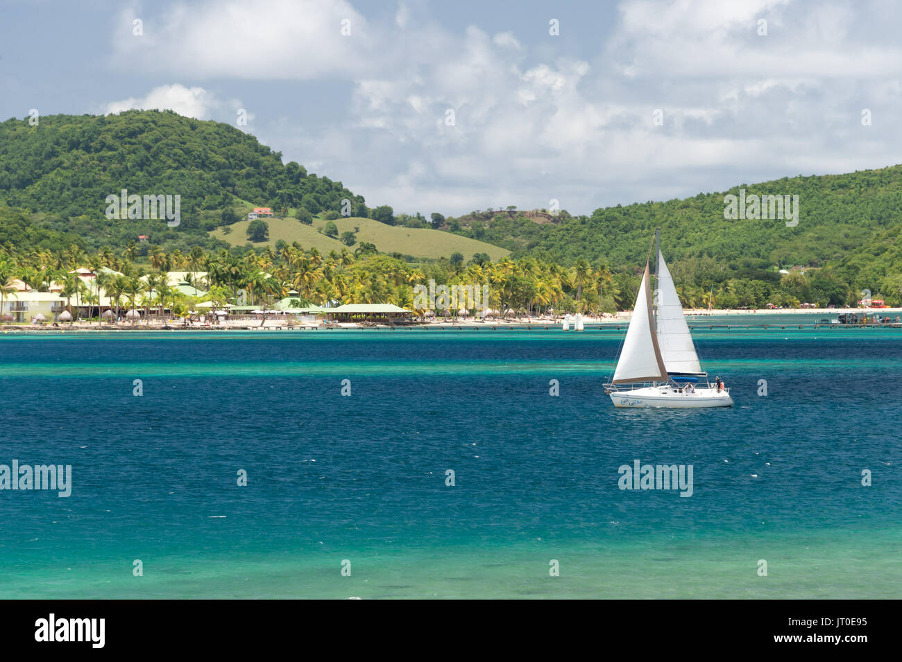 Sailboat sailing on Baie du Marin, Martinique, Caribbean, and Club Med resort in background - Stock Image