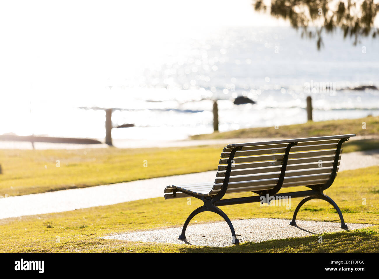 An empty park seat by the sea and beach, backlit by vibrant, bright morning sun light with no people in sight. - Stock Image