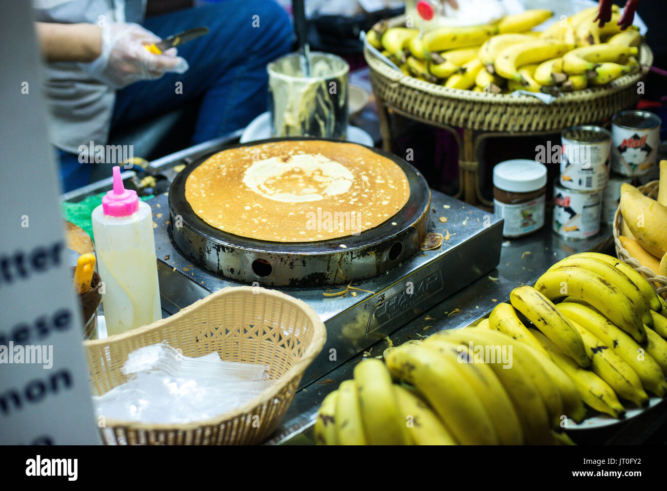 PATONG BEACH, THAILAND - 19 MAY 2017: Nightlife in Thailand. Street food. A prepares a pancake with chocolate in the street. - Stock Image