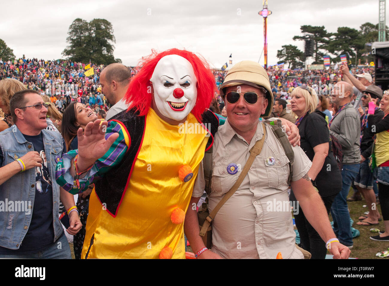 Festival goers dressed in Pennywise The Clown and Safari Suit fancy dress at Rewind North Festival, Capesthorne Hall, Cheshire UK. - Stock Image