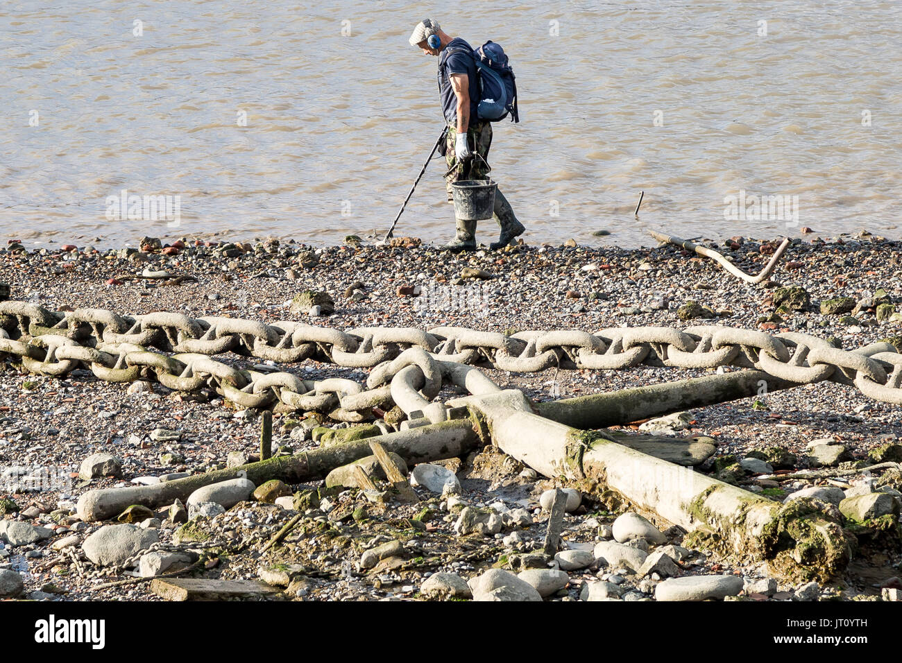 London, UK. 7th August, 2017. An afternoon mudlarker scans the River Thames foreshore near Greenwich with a metal detector searching for remnants of the past. © Guy Corbishley/Alamy Live News - Stock Image