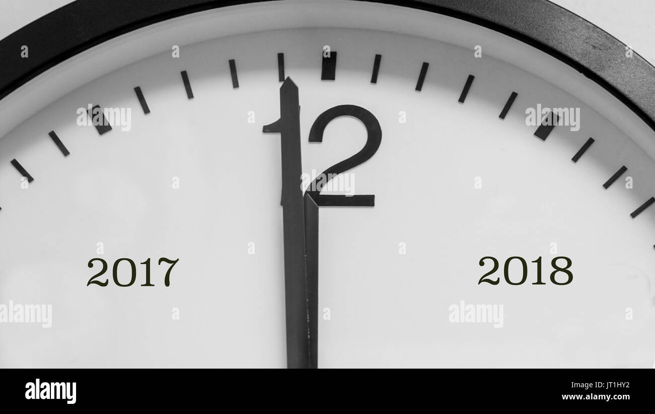 Closeup on the black pointers of a white background round clock marking a minute before midnight, marking the end of year 2017 and beginning of 2018. - Stock Image