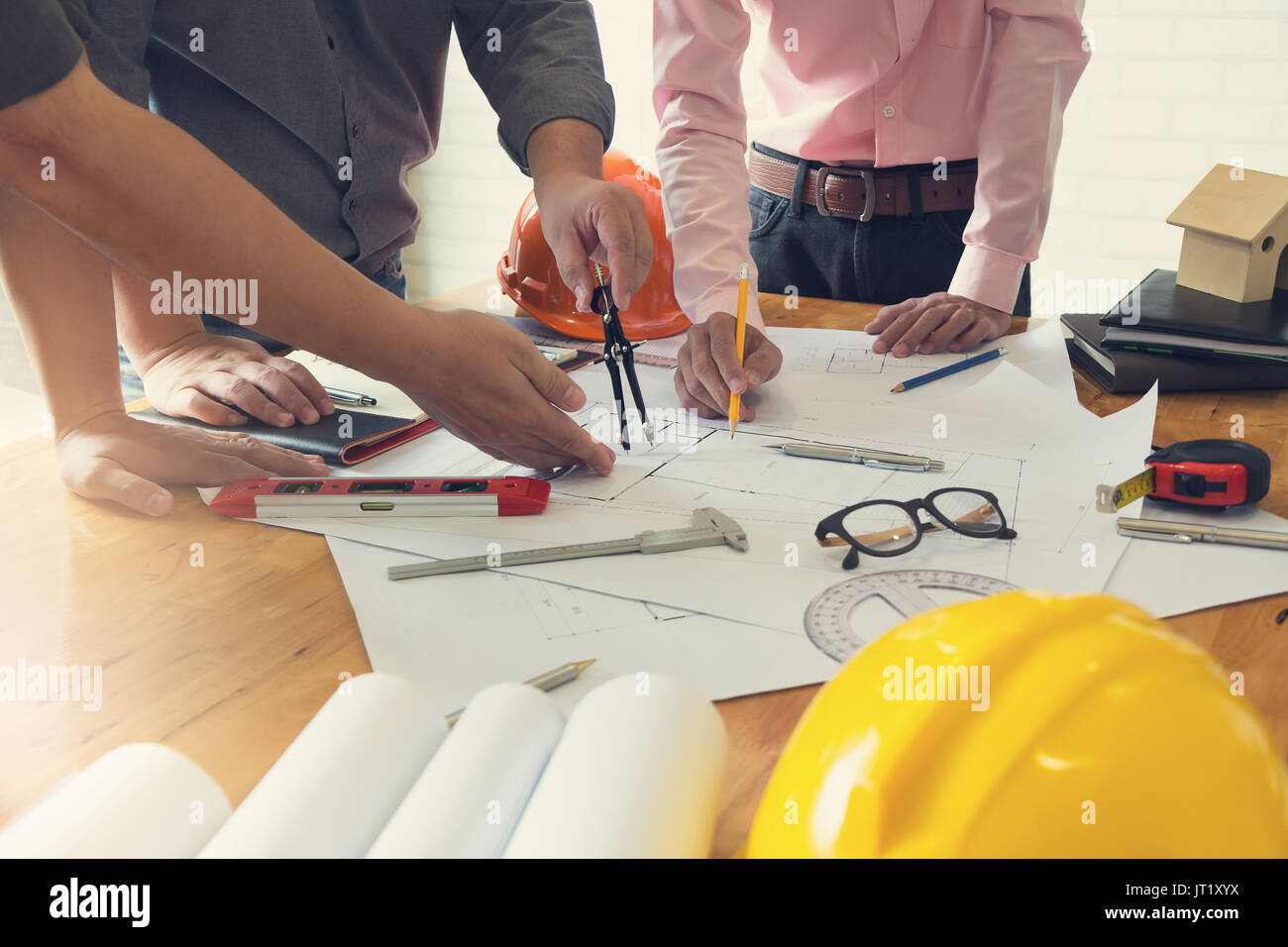 Engineer and Architect concept, Engineer Architects office team working and discussing house plan with blueprints and house model, Vintage Effect - Stock Image