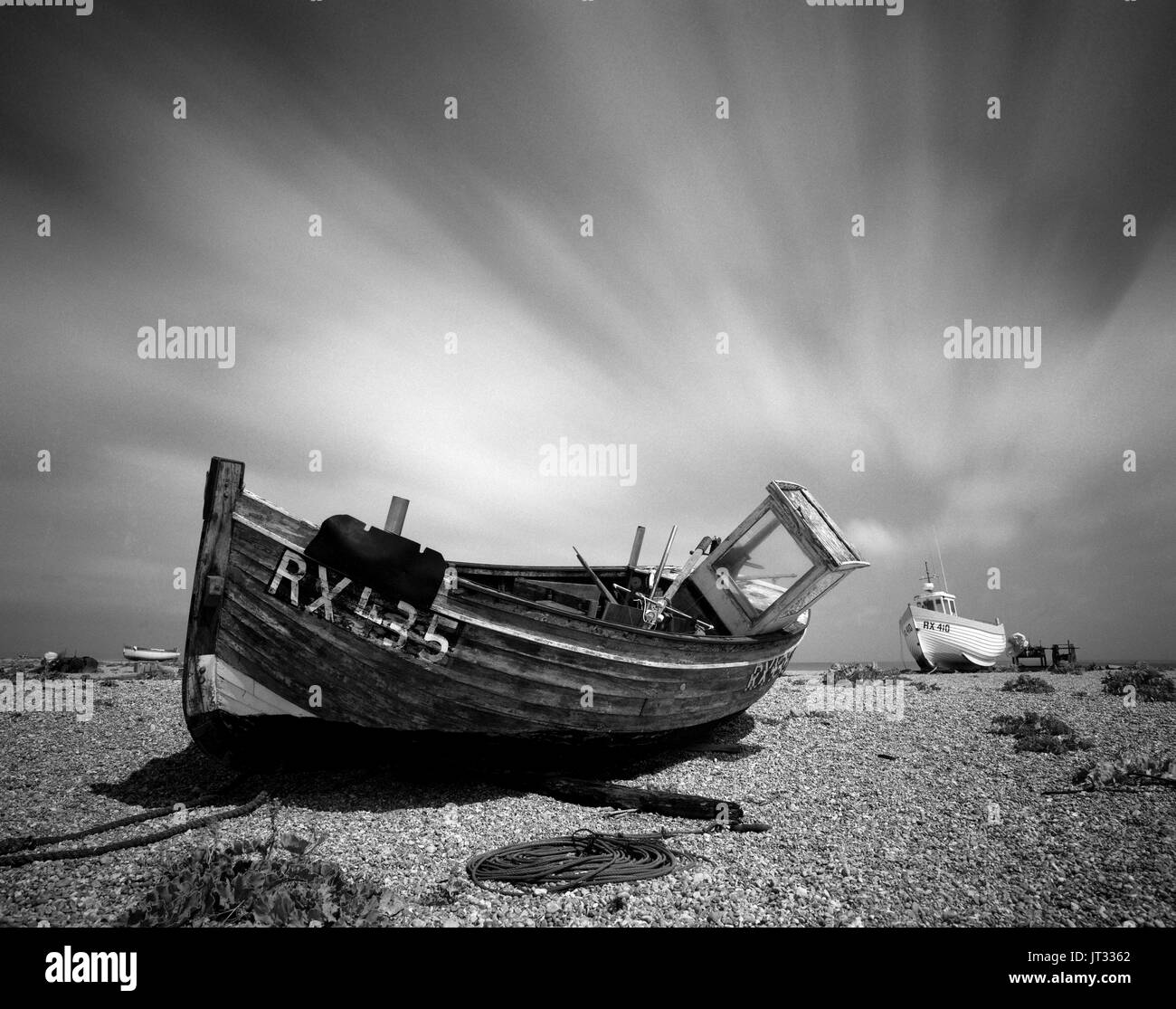 An old fishing boat in need of repair on the shingle beach at the National Nature reserve, Dungeness Kent, - Stock Image