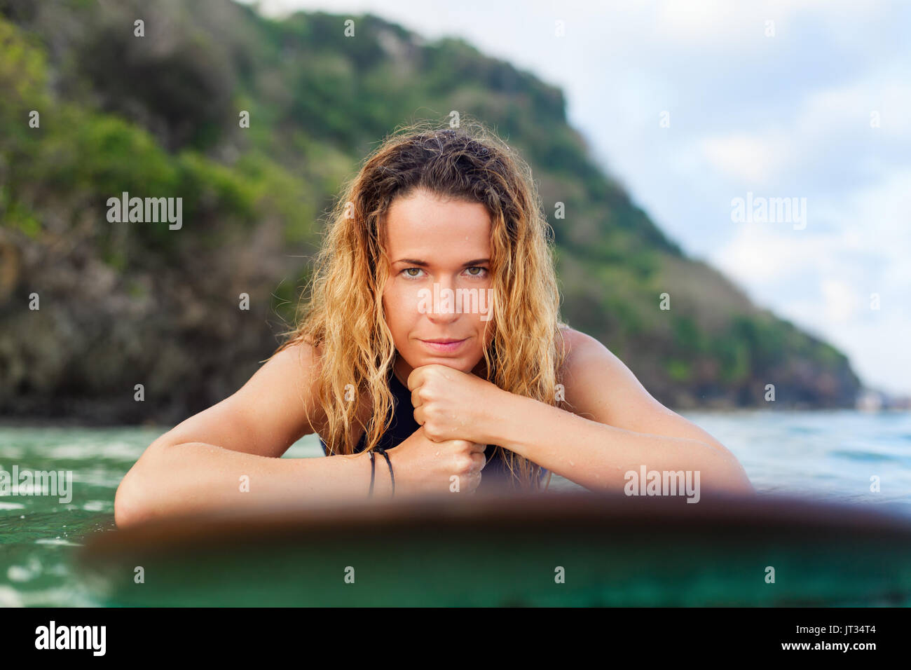 Happy girl in bikini have fun before surfing Surfer lie on surf board, look at sunset sky. People in water sport adventure camp, extreme activity on f - Stock Image