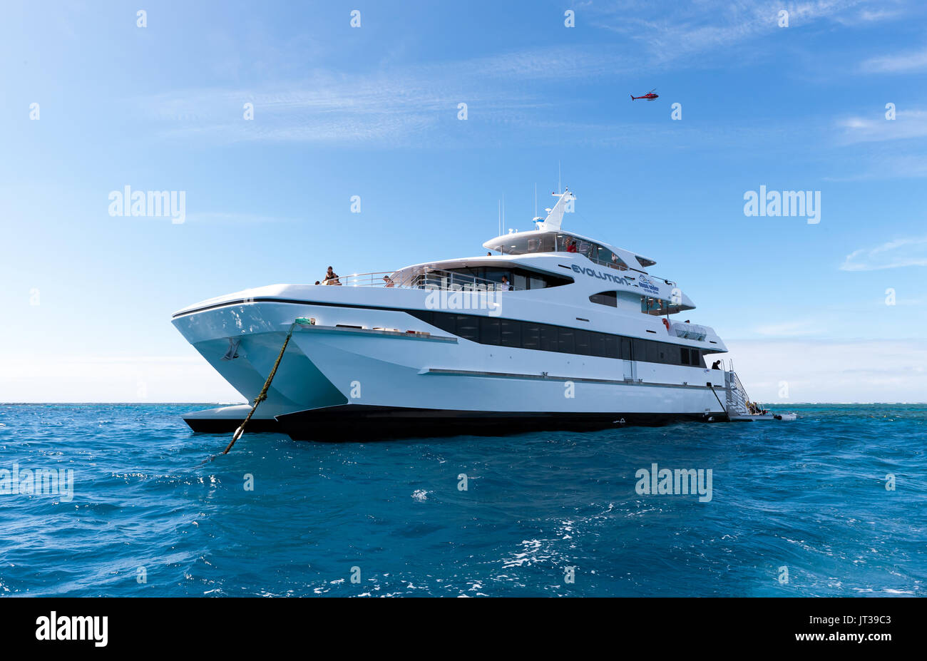 The Evolution, a 33 meter commercial catamaran operated by the Down Under Cruise and Dive Company, moored off Hastings Reef  Cairns - Stock Image