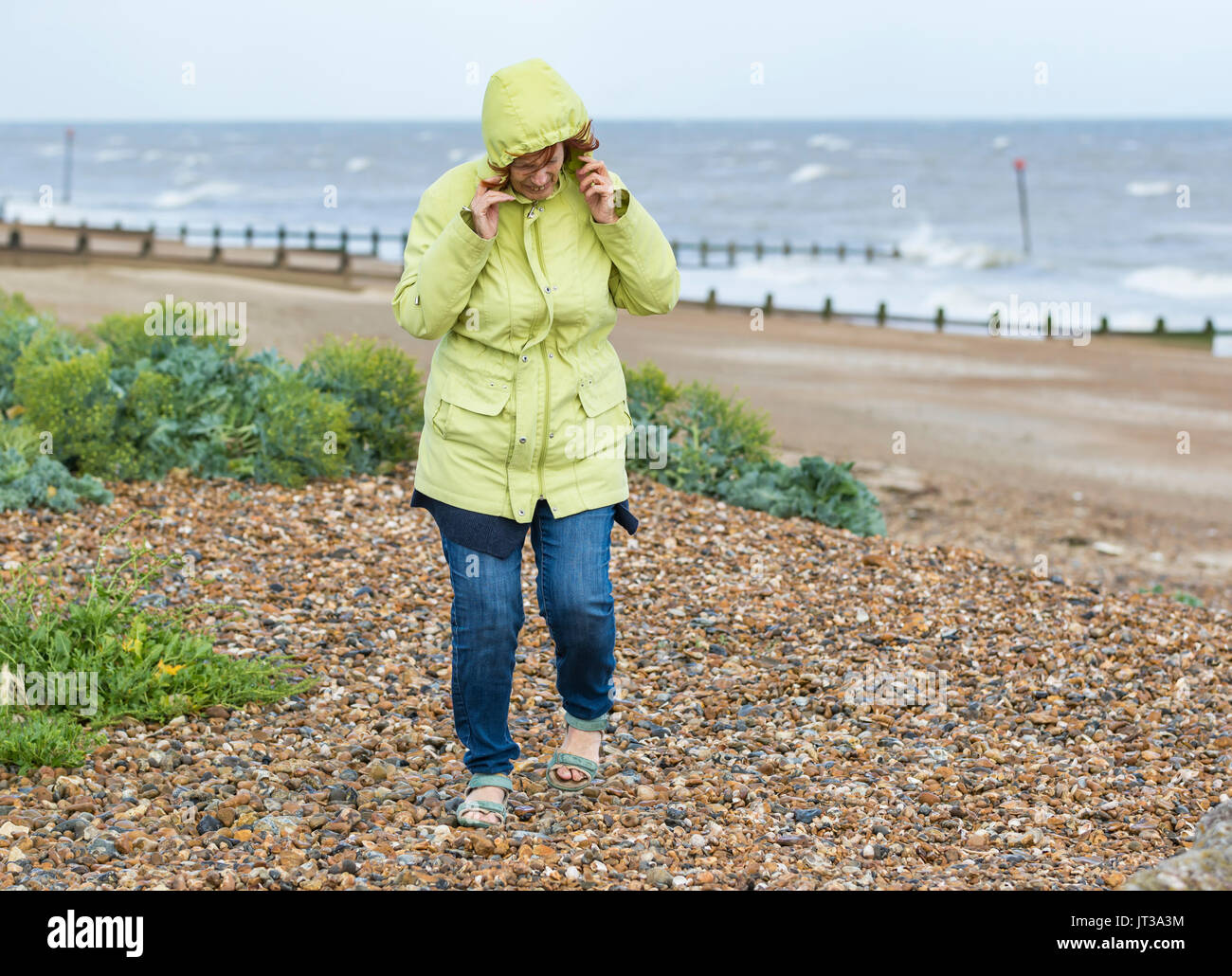 Elderly / Middle aged woman on a beach on a cold windy day in the UK. - Stock Image