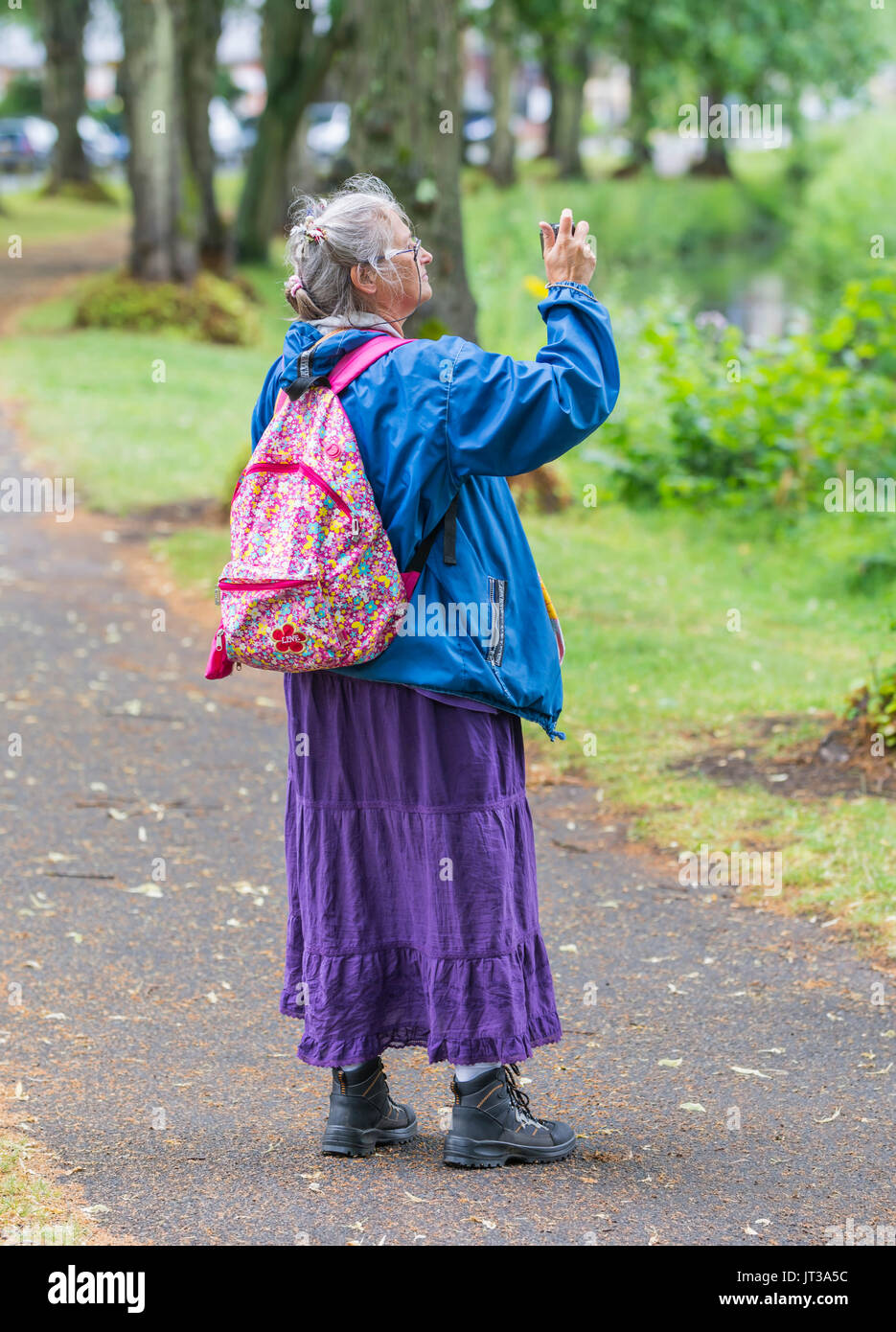 Elderly woman with a backpack taking photos. - Stock Image