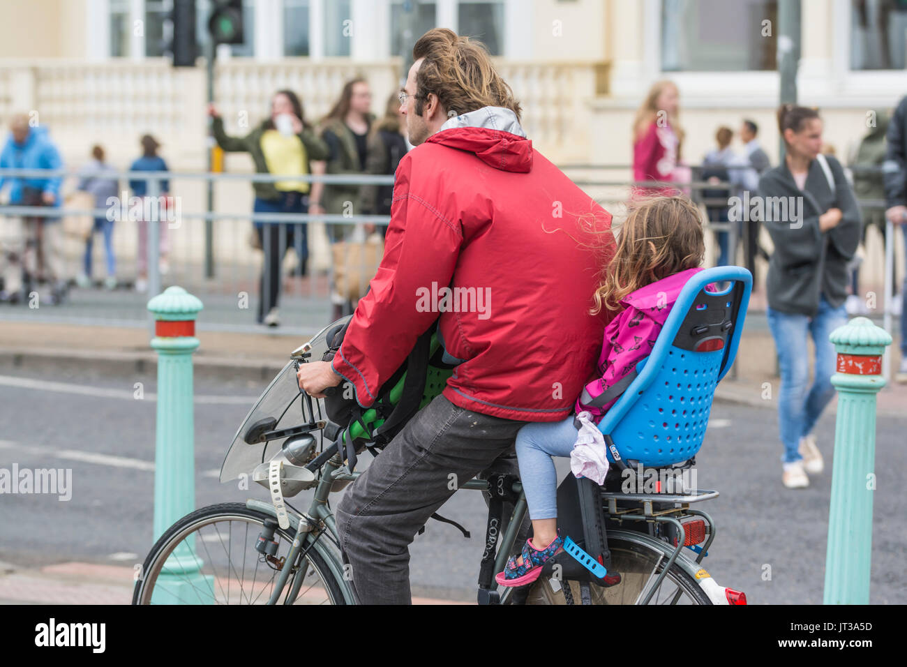 Man cycling with a child in a child's seat, both not wearing a helmet. Irresponsible cyclist. - Stock Image