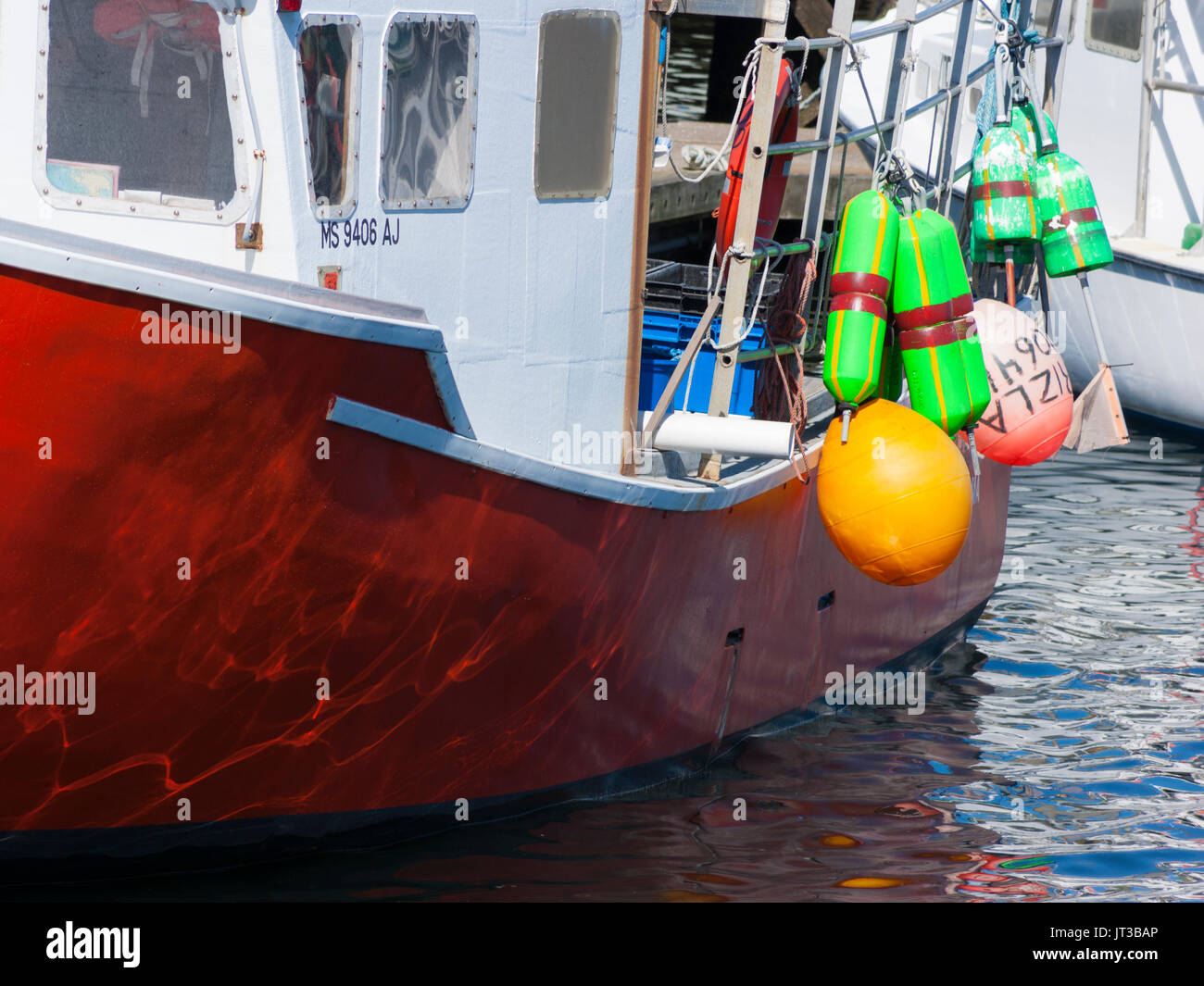 Buoys and fenders hanging on the side of a lobster boat. Gloucester Harbor, Cape Ann, Massachusetts. - Stock Image