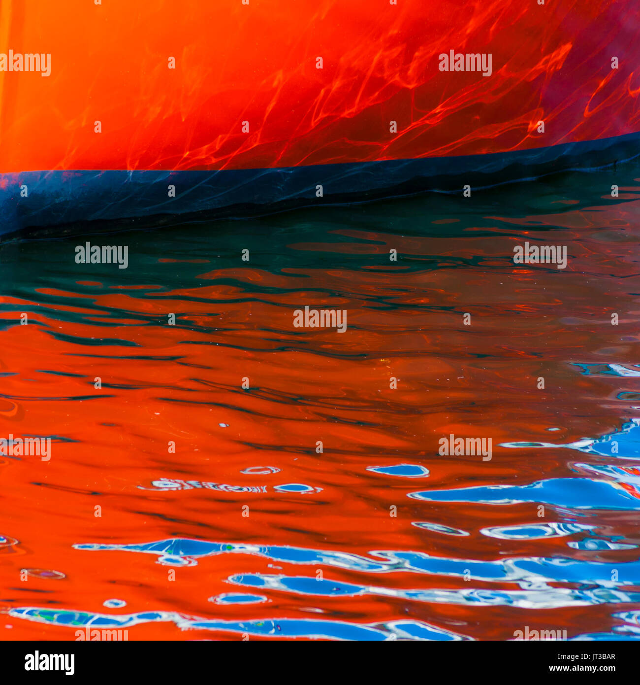 Boat hull reflected on rippled water. - Stock Image