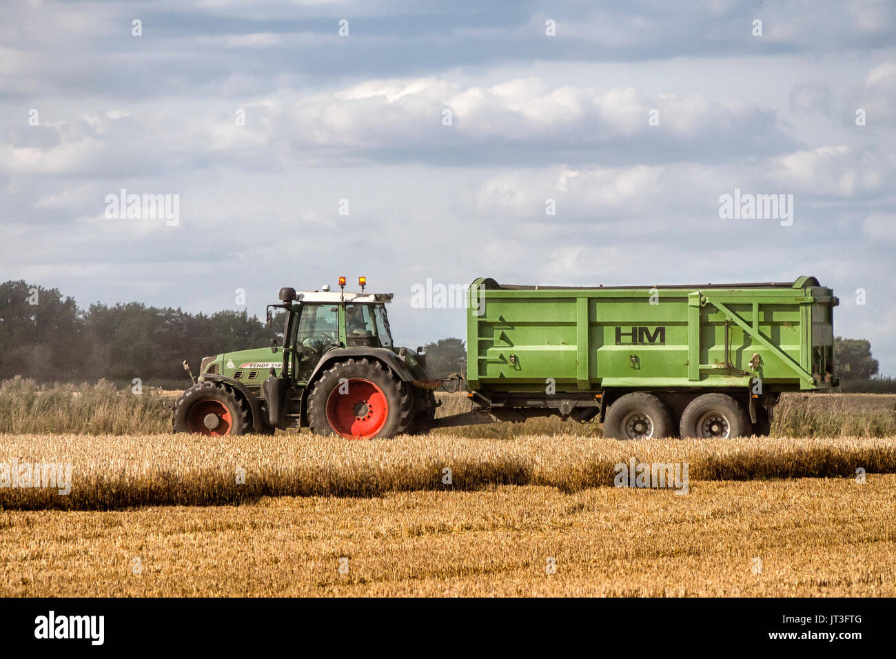 Tractor and Trailer waiting to be called to take-off harvested grain during Harvest. - Stock Image