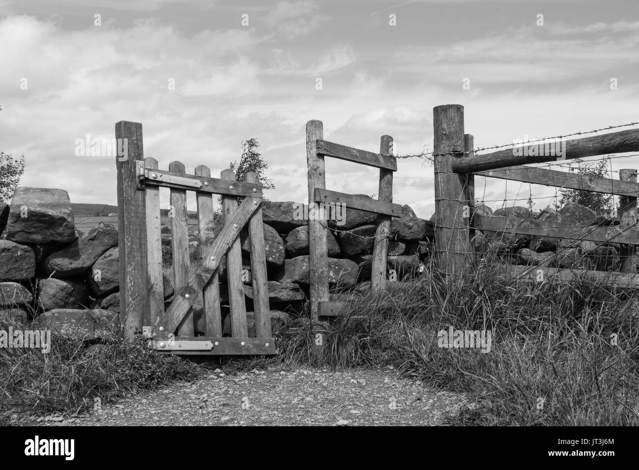 A rustic, slanted wooden gate in a traditional stone wall separating fields in the rural Lancashire countryside. Black and white - Stock Image