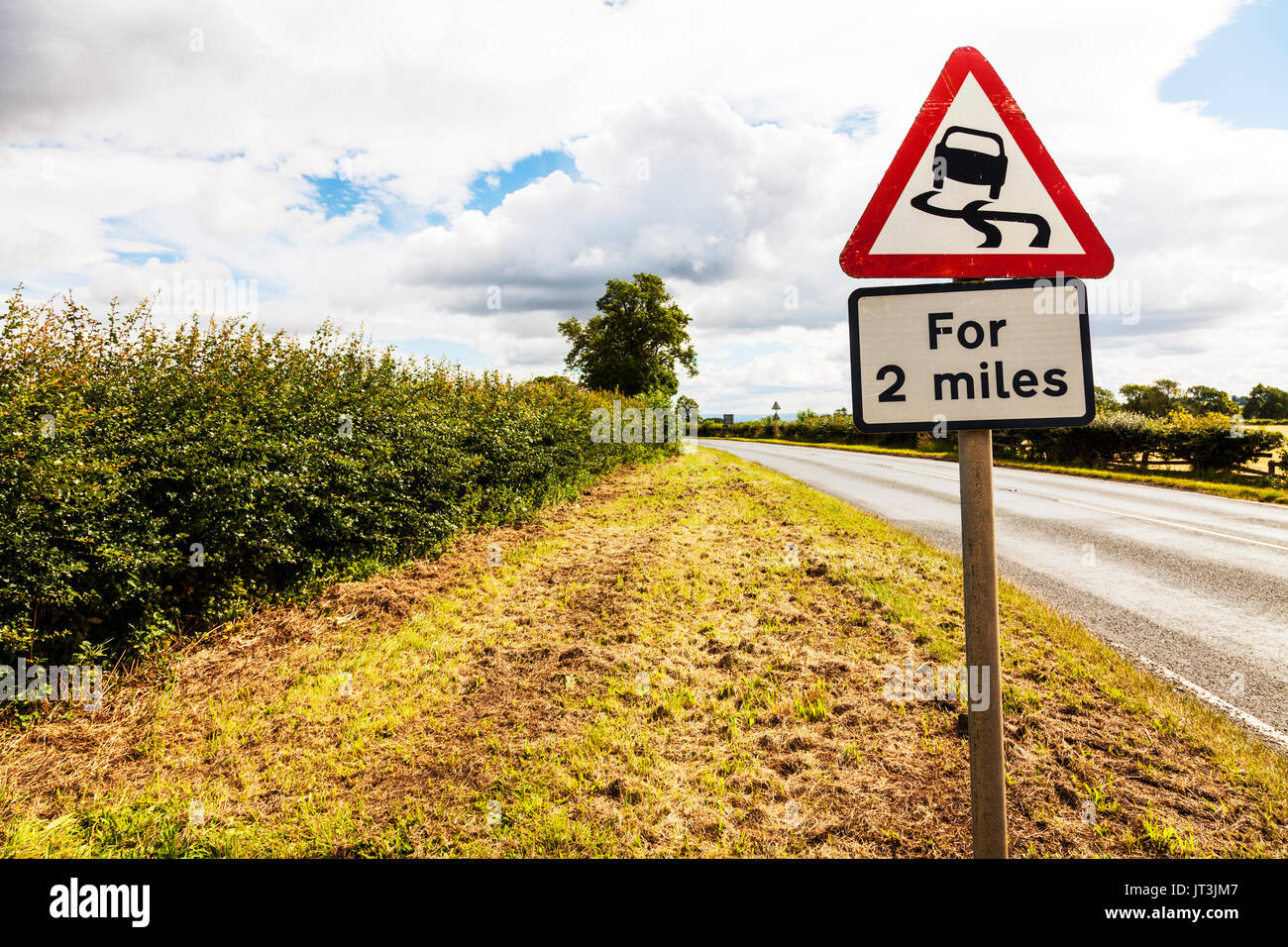 Slippery road, Slippery road UK road sign, for 2 miles, Slippery road for 2 miles, road sign, warning, danger, beware, UK, England, UK road signs - Stock Image