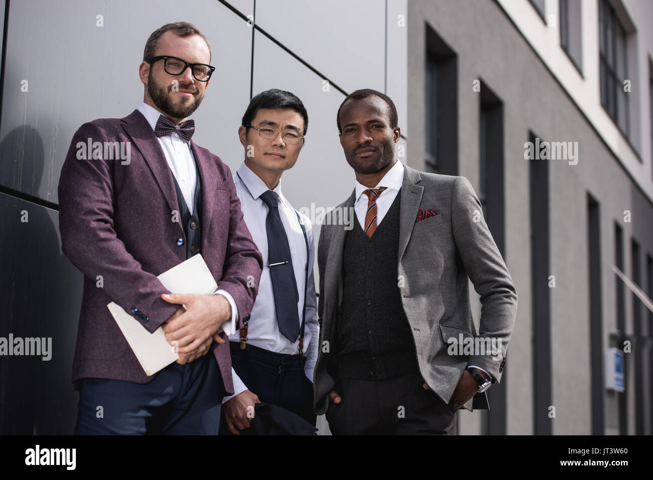 young stylish multiethnic businessmen in formalwear posing outdoors, business team meeting - Stock Image