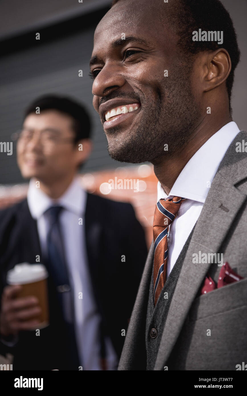 young smiling multiethnic businessmen meeting at coffee break outdoors, business team meeting - Stock Image