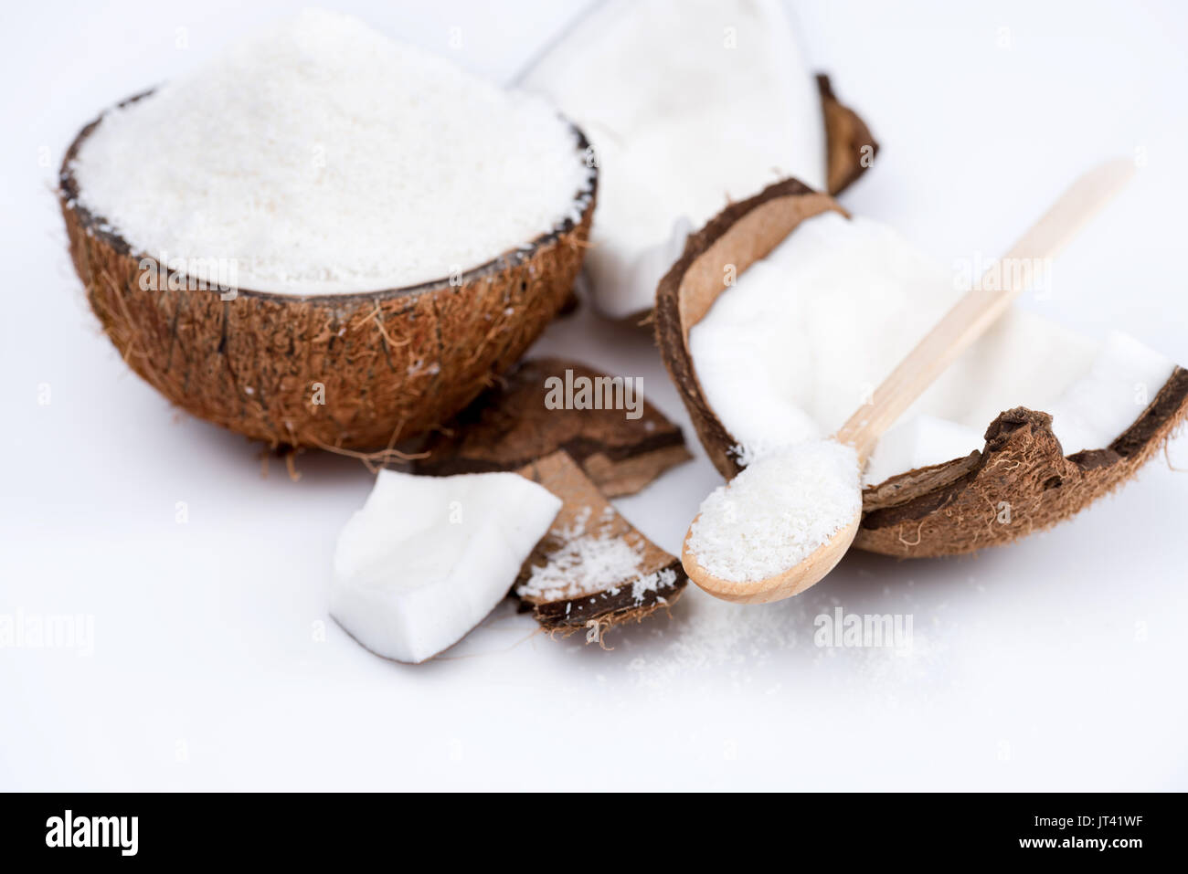 ripe organic coconut with sweet shavings with wooden spoon isolated on white   - Stock Image