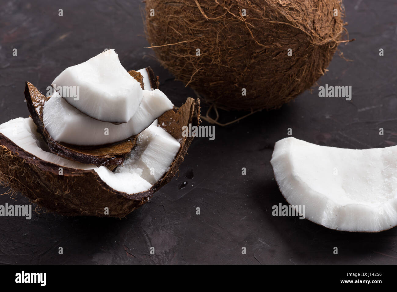 close up of pieces of ripe tropical coconut on dark background - Stock Image