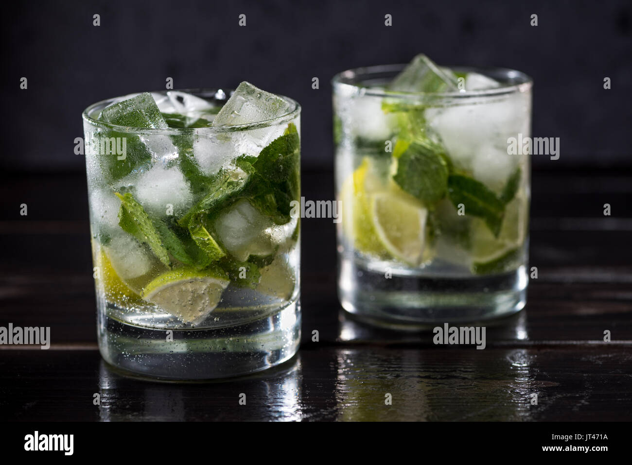 Close-up view of mojito cocktail in glasses on dark wooden table, cocktail drinks concept - Stock Image