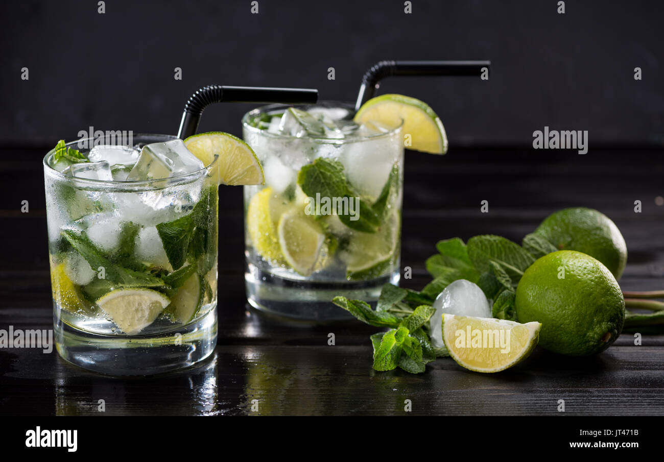 Close-up view of mojito cocktail in glasses, mint and limes on black, cocktail drinks concept - Stock Image