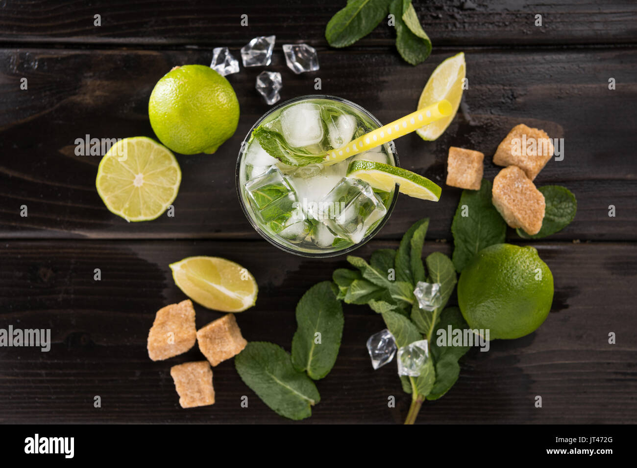 Top view of mojito cocktail in glass and fresh ingredients on dark wooden table top, cocktail drinks concept Stock Photo