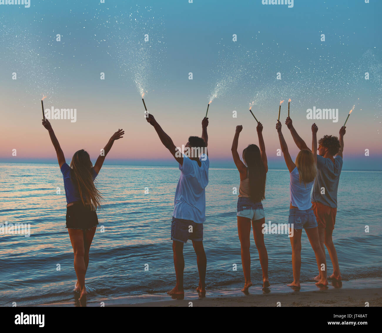Happy smiling friends at the beach with sparkling candles - Stock Image