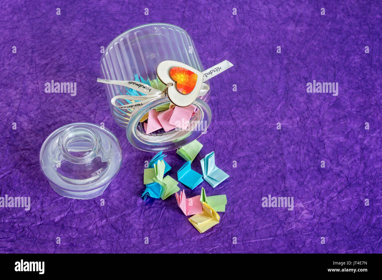 Toppled over glass jar with handmade wooden hearts decorations and ribbon full of colorful folded paper slips. Stock Photo