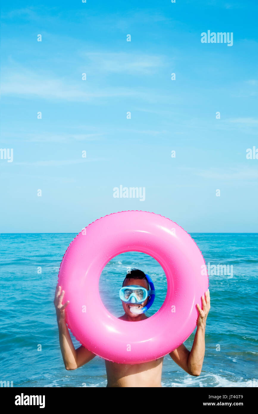 closeup of a young caucasian man wearing a diving mask and a snorkel popping up his face through the hole of a pink swim ring on the beach, with a neg - Stock Image