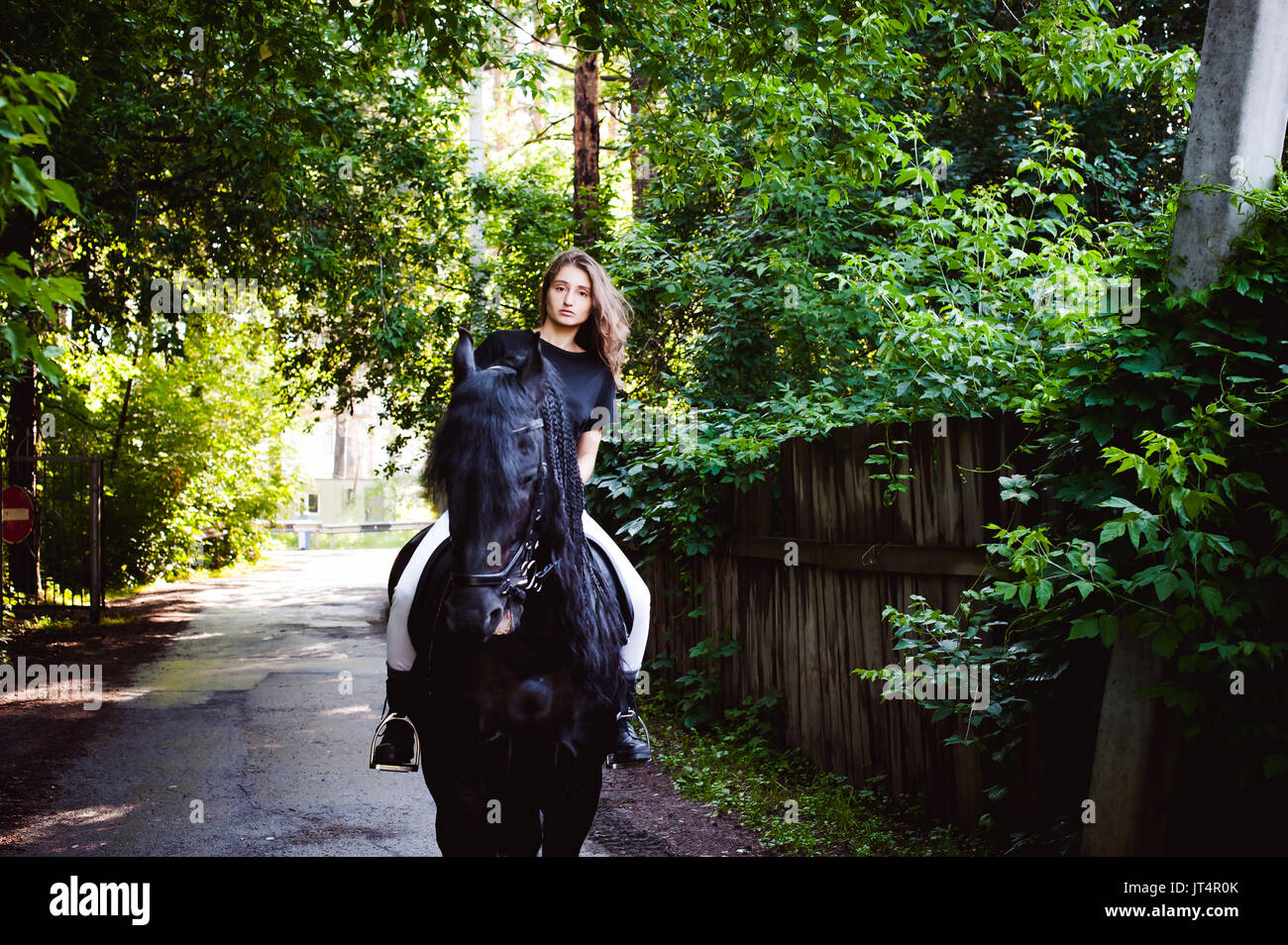 Emotional portrait of a horsewoman rider woman, astride, in love with horses, black Friesian stallion thoroughbred pet, outdoors - Stock Image