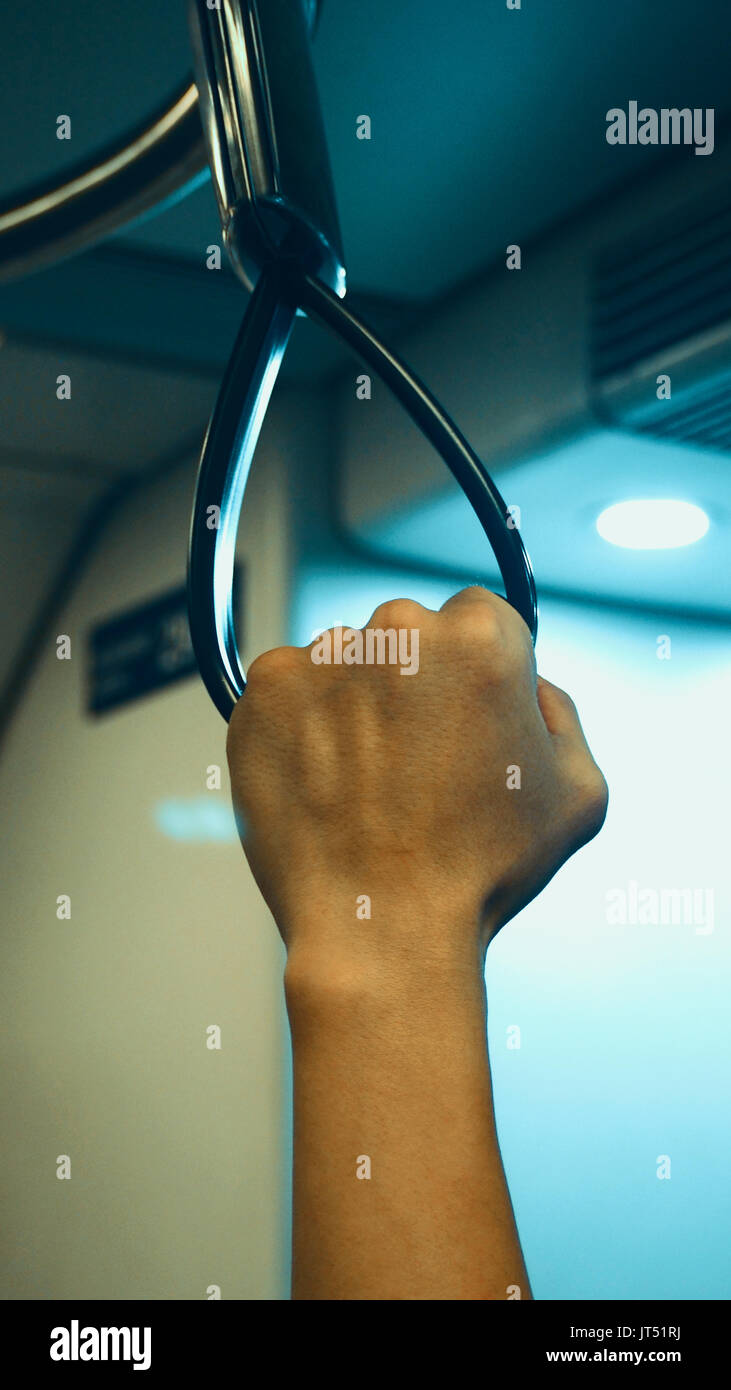 Big black color train handle and hand grabing for safety and travel by public transportation. Stock Photo