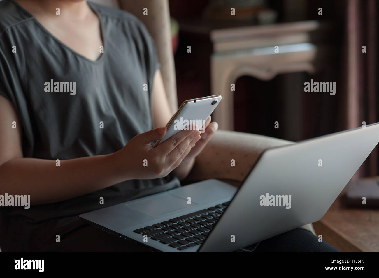 Woman freelancer using smartphone for social network while working with laptop computer. Online business and self-employed concept - Stock Image