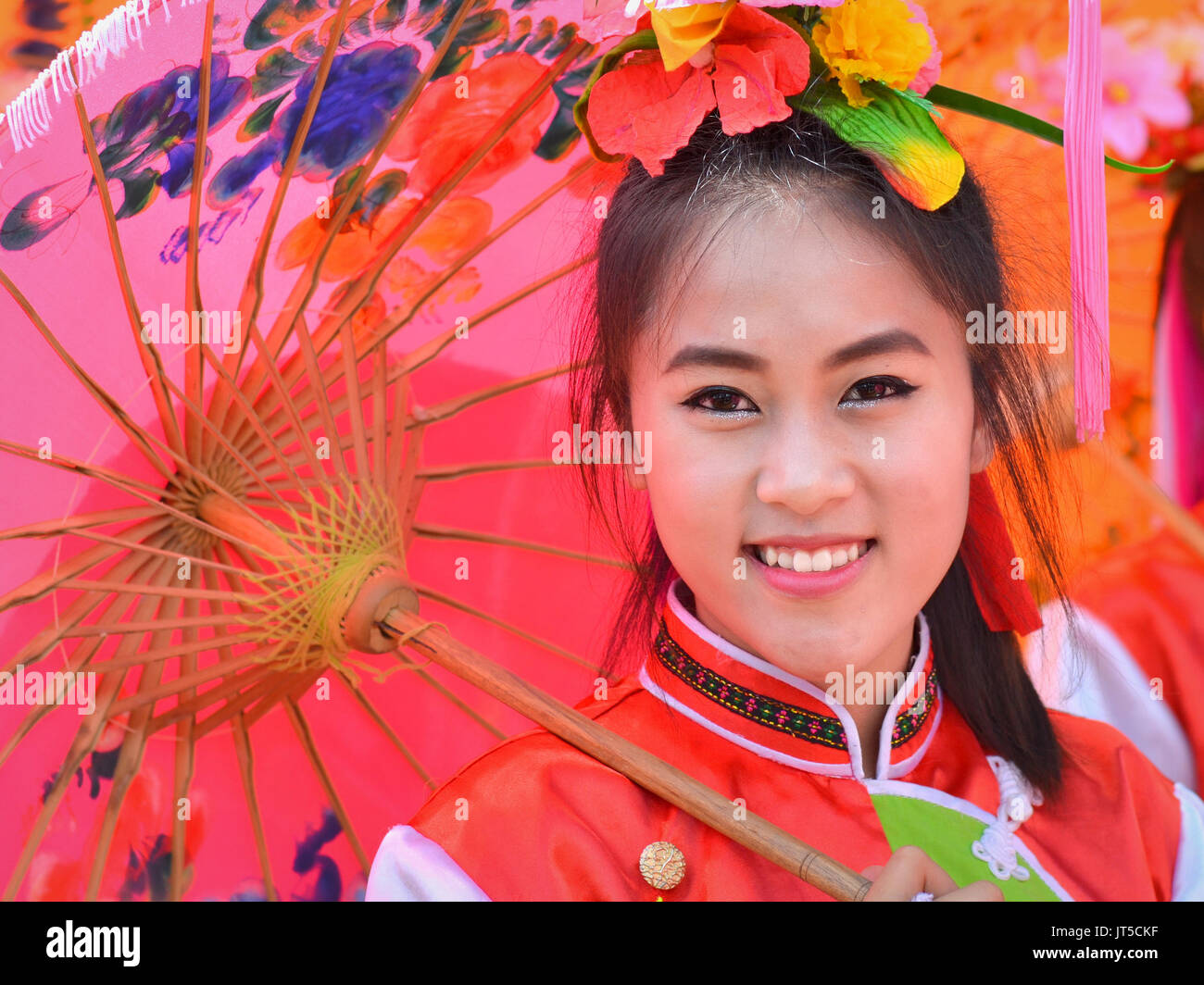 Smiling Thai Chinese Girl in Traditional Dress with Red Parasol (II), Northern Thailand. - Stock Image
