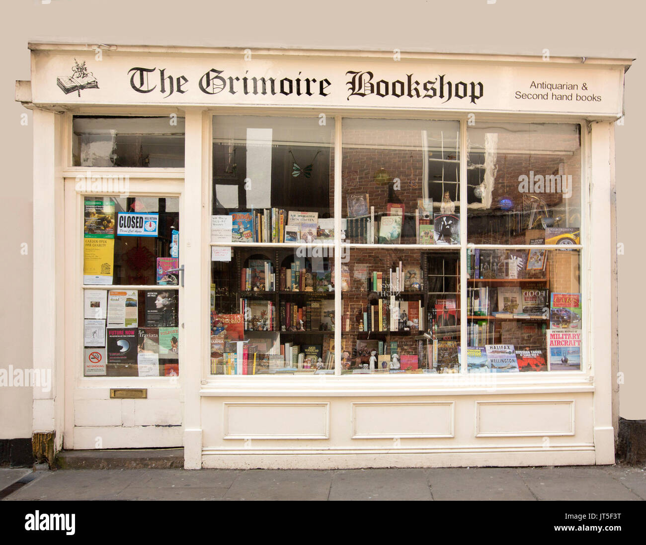 Second-hand bookshop, The Grimoire, neat cream painted facade with window of old building crammed with books, in historic city of York, England - Stock Image