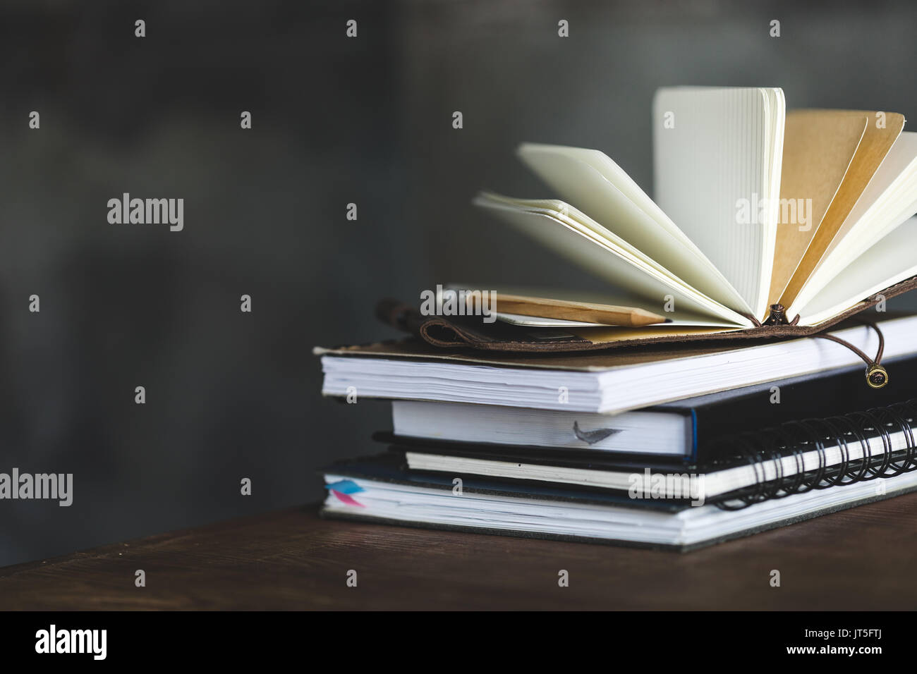 stack of books and diaries on dark grey with copy space Stock Photo