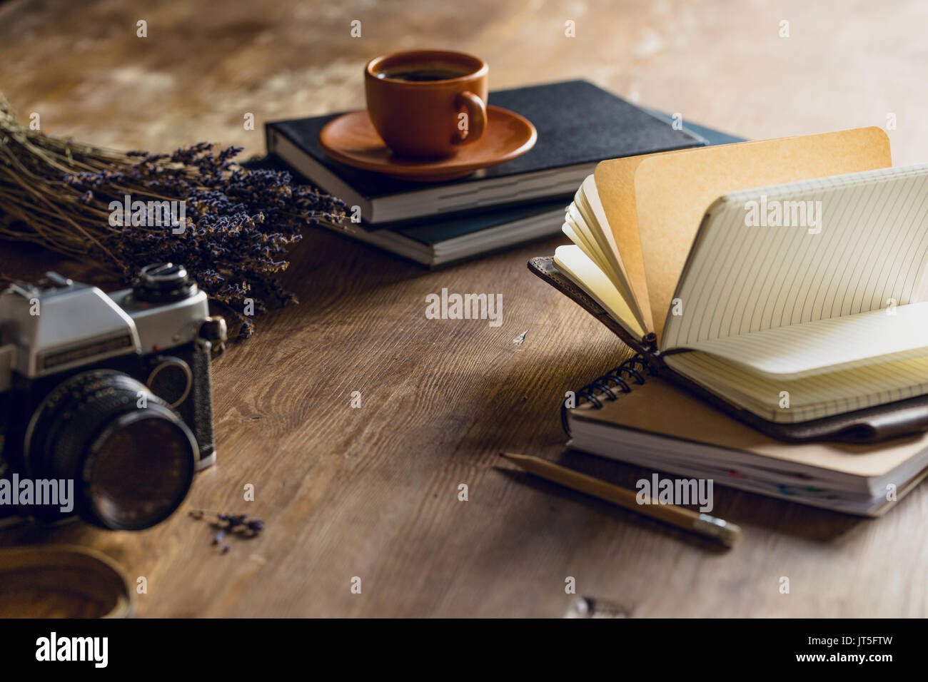 vintage photo camera, and diaries and cup of coffee on wooden tabletop - Stock Image