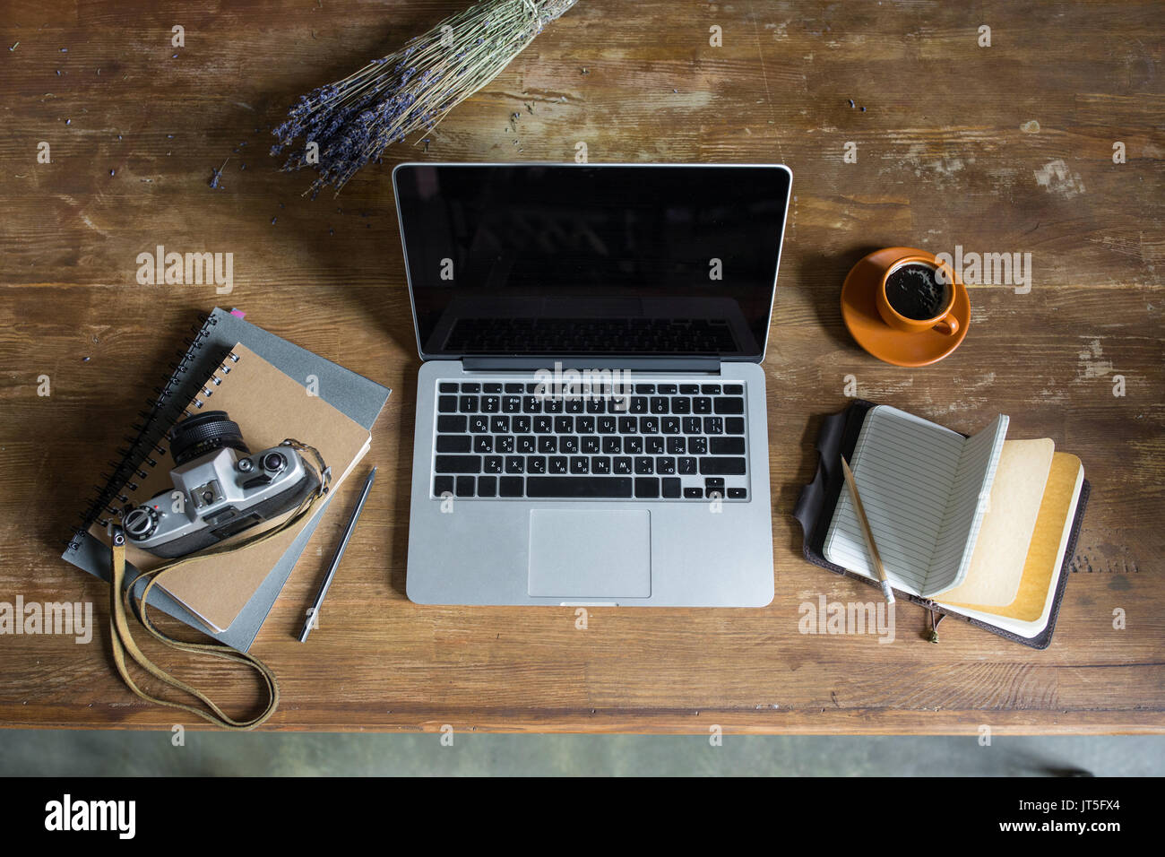 top view of laptop, diaries, vintage photo camera and cup of coffee on wooden tabletop - Stock Image