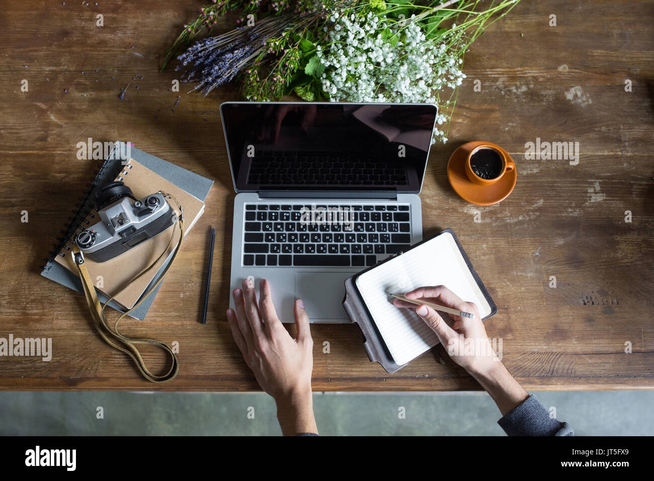person using laptop and graphic tablet at workspace with notebooks and vintage camera - Stock Image
