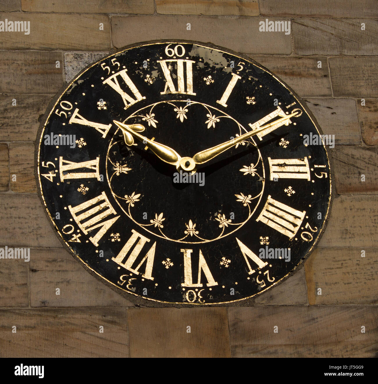 Large clock with black face and gold Roman numerals on brick wall of city building in York, England - Stock Image
