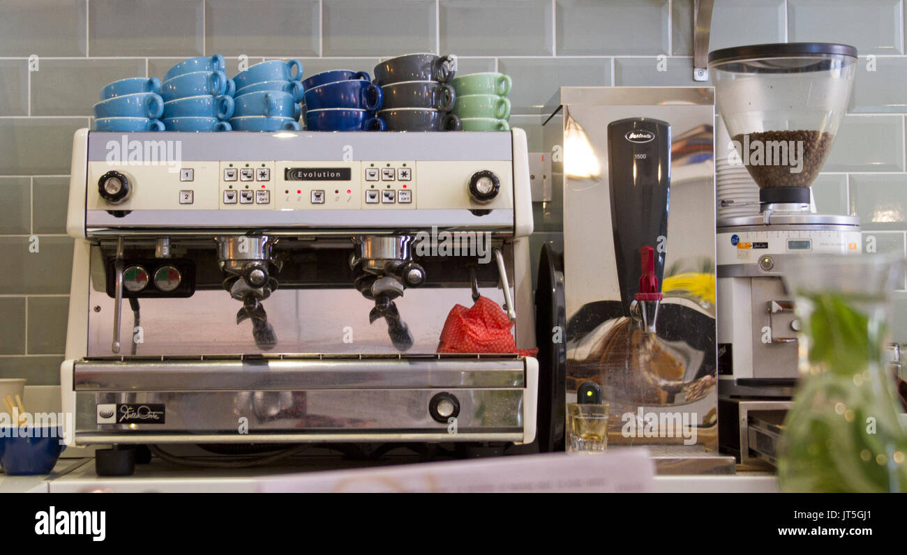 Coffee machine with stacks of colourful cups beside coffee grinding machine against grey tiled wall in cafe - Stock Image